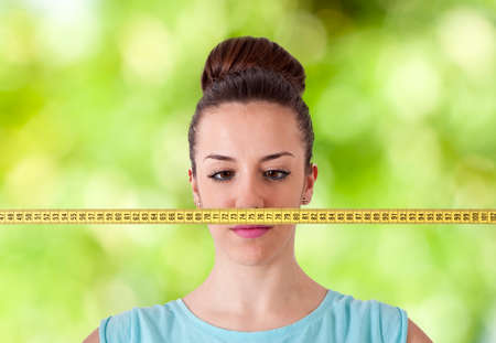 kilos: woman with tape measure worried about weight