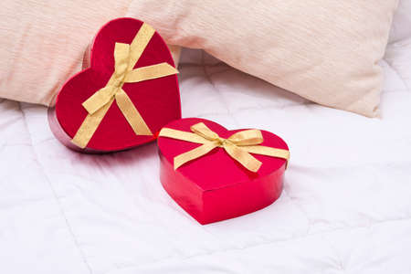 honeymooners: gift boxes with heart shape in the bedroom