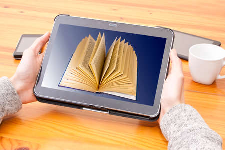 ibook: hands with tablet and digital book Stock Photo
