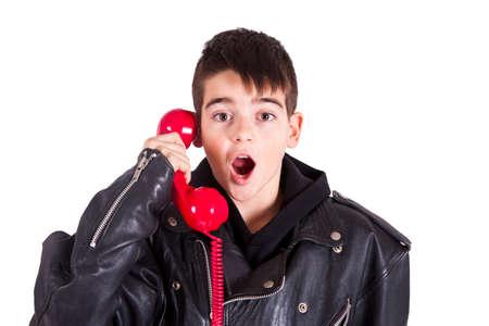 niños riendose: muchacho con el teléfono de la vendimia roja y cara de la sorpresa
