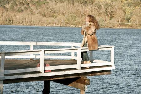 mujer mirando el horizonte: Mujer en el muelle mirando el paisaje Foto de archivo
