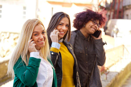 light hearted: young people with smartphone on street Stock Photo
