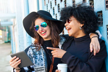 informal clothing: friends on the street with the tablet