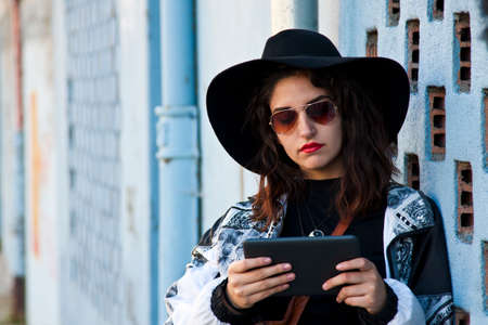 informal clothing: modern girl with the tablet on the street