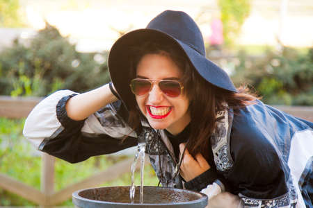 lighthearted: fashion girl drinking at source