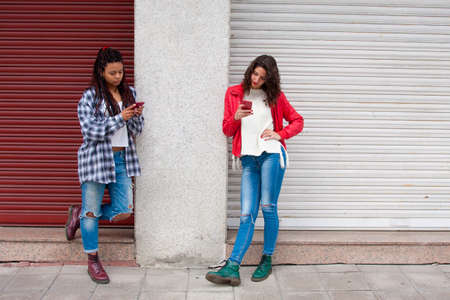 portability: girls on the street with mobile phone
