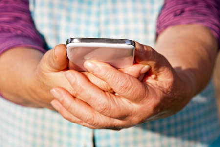 hands of senior woman with mobile