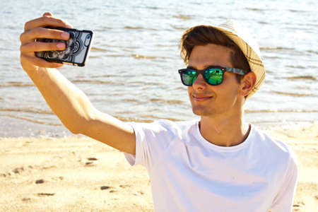selfy: man getting a photo with mobile phone on the beach. Sunset and soft summer light Stock Photo