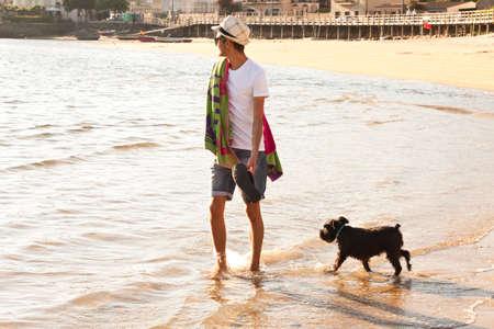 fidelidad: hombre caminando con el perro en la playa. noche de verano, la luz suave