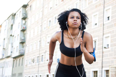 sportwoman: young woman running in the city