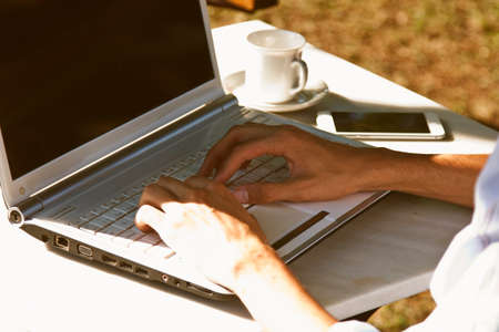 entrepreneurial: hands typing on laptop outdoors at sunset Stock Photo