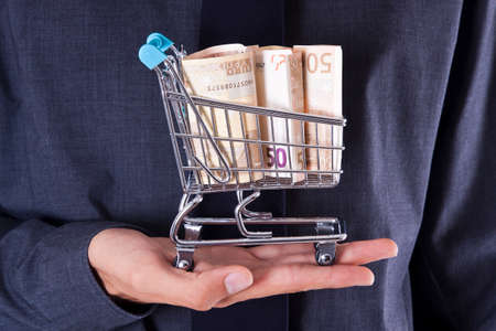 rebates: hand with money in shopping cart