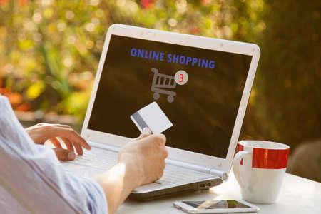 compras compulsivas: manos del hombre joven con ordenador portátil y carro de compras