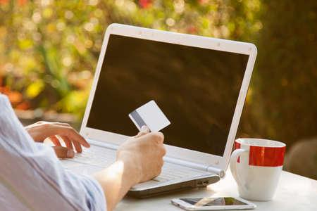 compras compulsivas: manos con tarjetas de crédito y compra en línea portátil