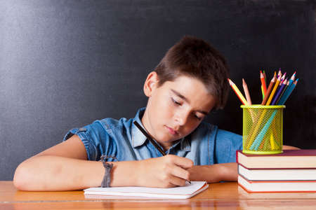 academia: child writing in the school table Stock Photo