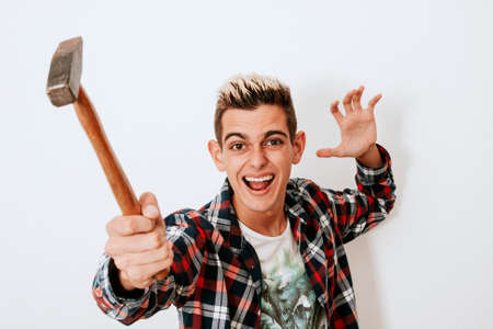 aftersales: young man with hammer striking Stock Photo