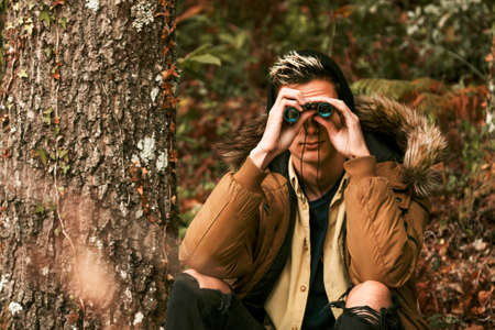man with map and binoculars in the woods