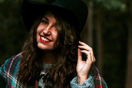 committed: portrait of young woman with hat in the woods
