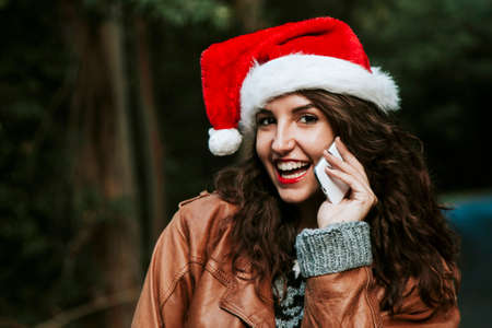 girl with christmas hat talking on mobile phone Stock Photo