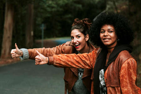 hitchhiking: two girls making funny hitchhiking