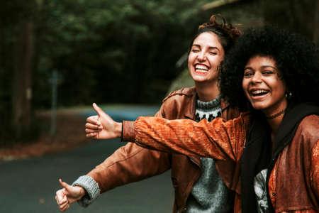 two girls making funny hitchhiking
