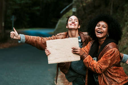 hitch hiker: girl hitchhiking with poster