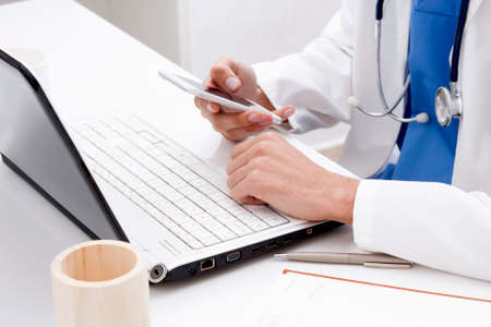 doctor with mobile phone in hands in office Standard-Bild