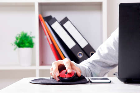 input device: hand on computer mouse in closeup