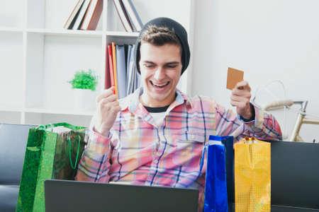 compras compulsivas: hombre en casa de compra en línea