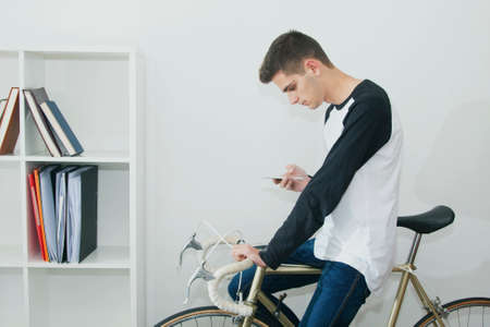 original bike: young woman with mobile phone in the house with the bike and the shelf wall Stock Photo