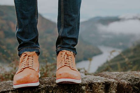 feet with hiking boots with the mountains in the background, concept of adventure and travelers