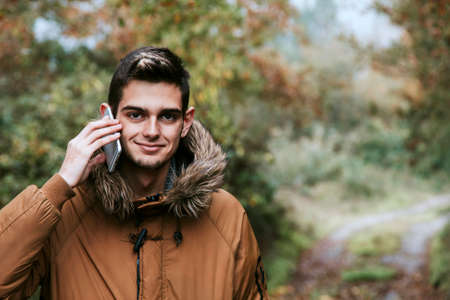 young boy with cellphone in winter