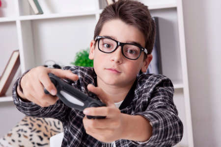 child at home playing with the video games or game console Stock Photo