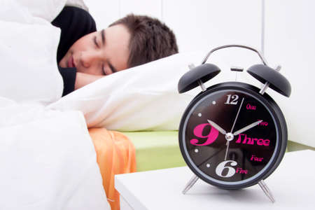 get tired: alarm clock in the foreground of the room with the child sleeping in bed