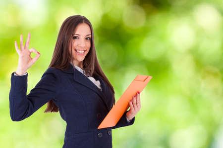 negocio de la mujer atractiva con el expediente y el signo de aprobación y la sonrisa aceptables