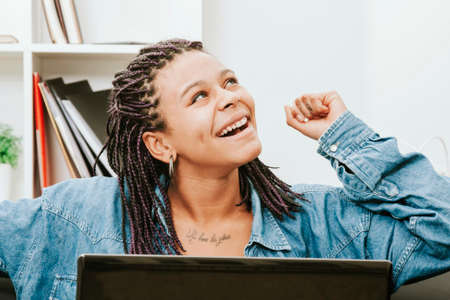 enthusiasm: female young african descent with the computer in house celebrating with enthusiasm Stock Photo