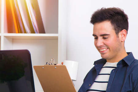 revisando documentos: young man reviewing documents having coffee on the desk with laptop computer