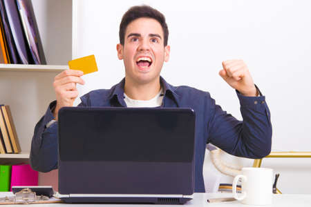 compulsive shopping: man with laptop celebrating enthusiastically buying online Foto de archivo