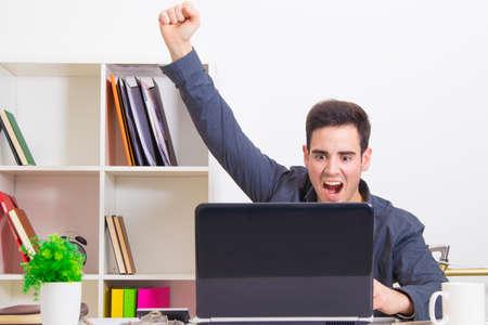 macho joven que celebra con entusiasmo que buscan que el ordenador portátil