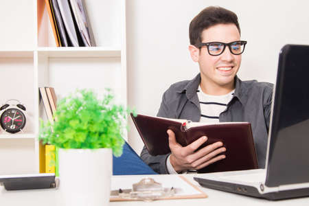 young man in house or office with the book or calendar and notebook computer