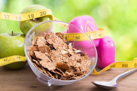 bowl of cereal with tape measure fruit and weights of fitness, diet concept