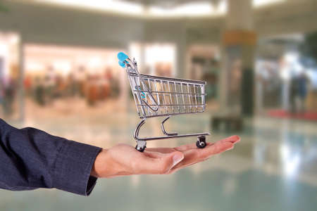 compras compulsivas: hand with the car of the purchase in the Center commercial
