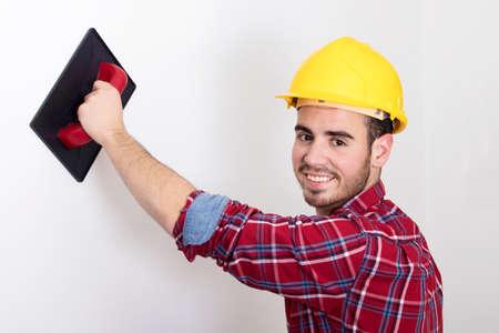 Albañil trabajando en la pared, sonriendo