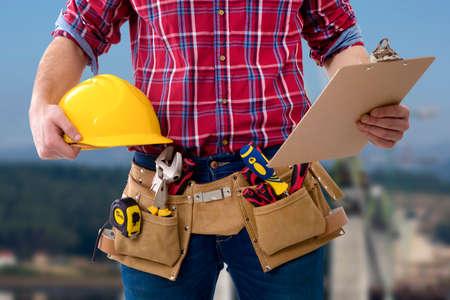 Close-up van de werknemer van de constructie met de helm en de map met de documenten Stockfoto - 71757139