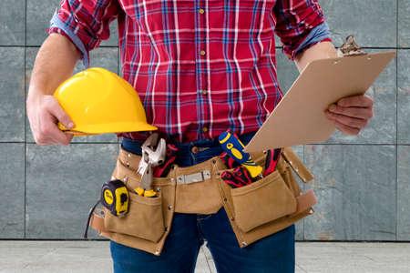 Close-up van de werknemer van de constructie met de helm en de map met de documenten Stockfoto - 71757134