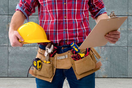 closeup of the worker of the construction with the helmet and the folder of the documents Standard-Bild