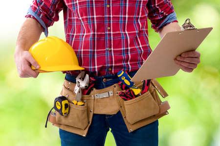 Close-up van de werknemer van de constructie met de helm en de map met de documenten Stockfoto - 71757155