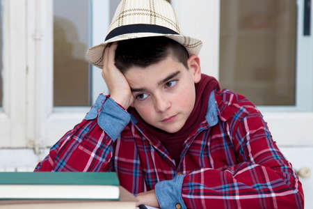 child with expression of bored and tired with school books Stock Photo