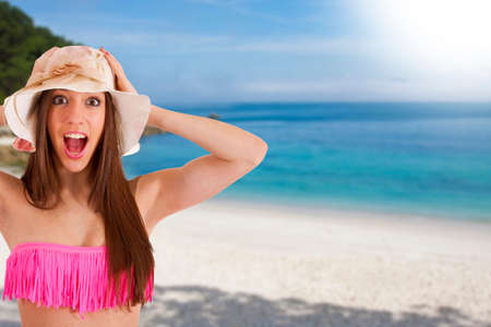 young woman on the beach in the summer with expression of surprise