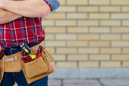 builder with the belt of tools on background to outdoor